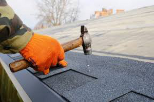 A roofer with an orange glove and a hammer installingshingles.